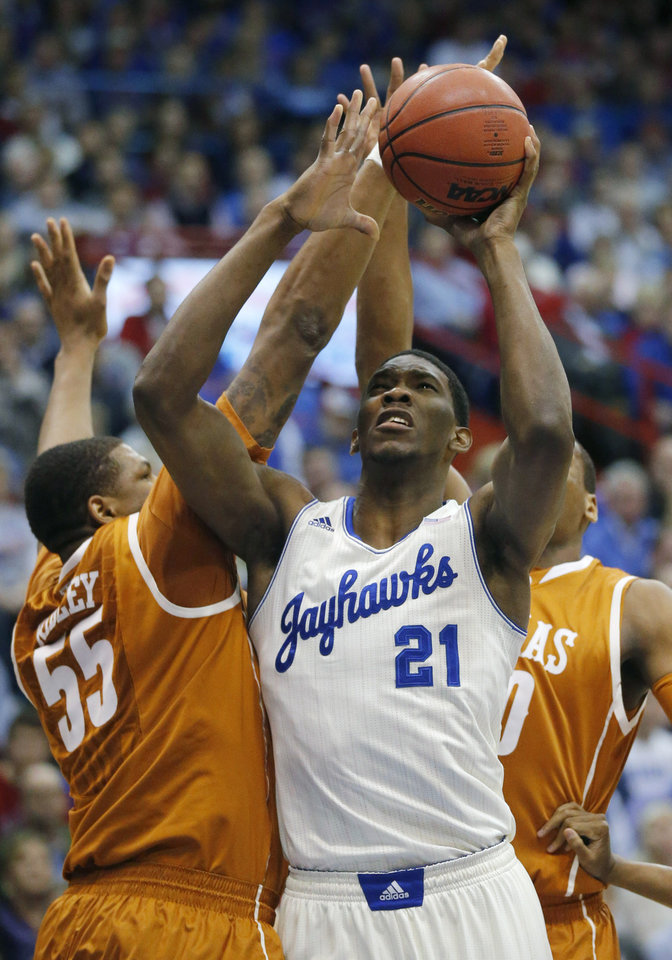 Photo - Kansas center Joel Embiid (21) shoots while covered by Texas center Cameron Ridley (55) and forward Jonathan Holmes, back, during the first half of an NCAA college basketball game in Lawrence, Kan., Saturday, Feb. 22, 2014. Embiid was fouled by Holmes on the play. (AP Photo/Orlin Wagner)