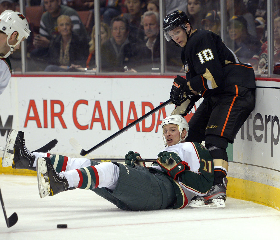 Minnesota Wild center Kyle Brodziak, below, and Anaheim Ducks right wing Corey Perry watch the puck during the second period of an NHL hockey game, Friday, Feb. 1, 2013, in Anaheim, Calif. (AP Photo/Mark J. Terrill)
