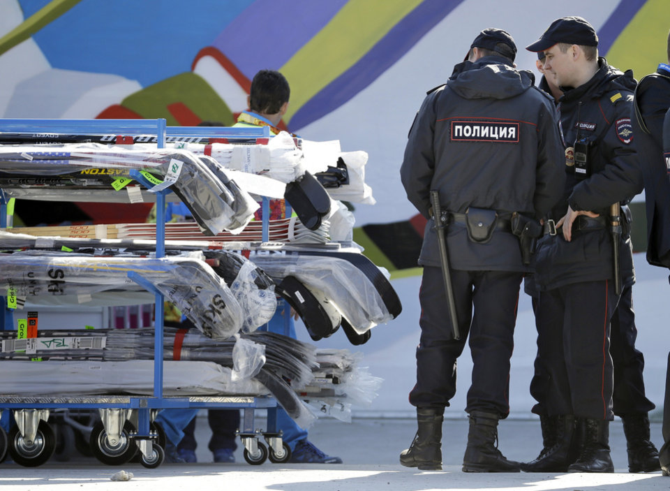 Photo - FILE - In this Feb. 10, 2014 file photo, police officers look over a cart of hockey sticks after they were taken off a plane as NHL hockey players arrive at the Sochi International Airport for the 2014 Winter Olympics, in Sochi, Russia.Sochi hotel guests are walking, unchecked, past unused metal detectors. Security guards are no longer poking around at the pockets and ankles of every single person entering Olympic facilities. Tangerines and bottles of Coke are making it through security barriers that banned them two weeks ago. For all the warnings that security in Sochi would be invasive and aggressive, it's appearing more uneven, and in places almost relaxed.  (AP Photo/Mark Humphrey, File)