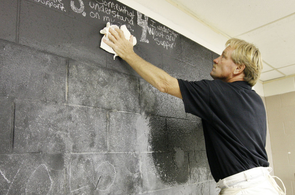 Photo - Maintenance worker Neal McDonald cleans a wall to be painted at  Jarman Middle School in Midwest City. Photo by Paul B. Southerland, The Oklahoman  PAUL B. SOUTHERLAND - PAUL B. SOUTHERLAND