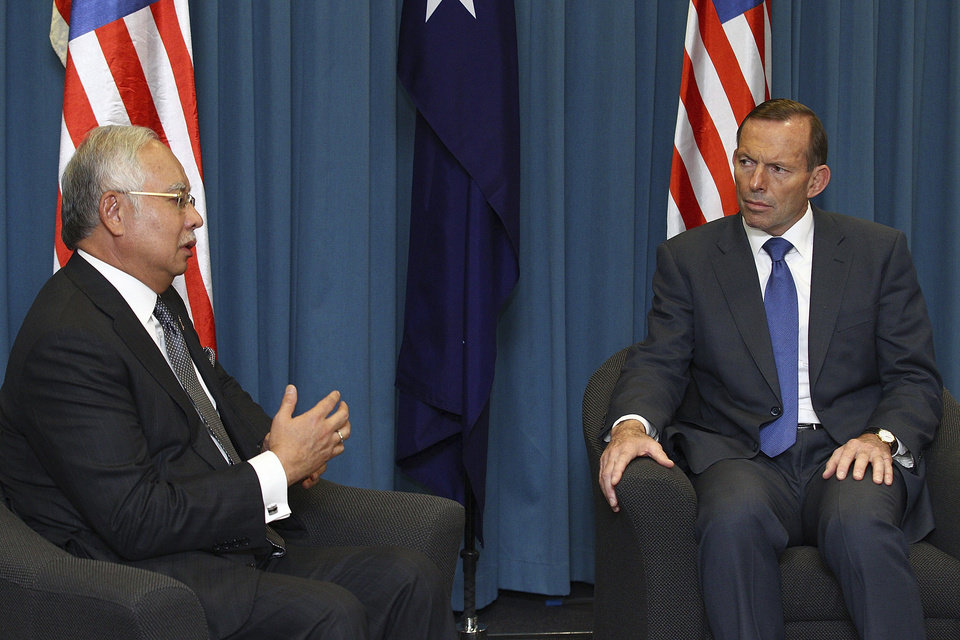 Photo - Malaysian Prime Minister Najib Razak, left, and Australian Prime Minister Tony Abbott talk during their meeting at the Commonwealth Parliament Offices Thursday, April 3, 2014 in Perth, Australia. The search for a missing Malaysia Airlines Flight MH370 continues but no trace of the Boeing 777 has been found nearly a month after it vanished in the early hours of March 8 on a flight from Kuala Lumpur to Beijing with 239 people on board. (AP Photo/Paul Kane, Pool)