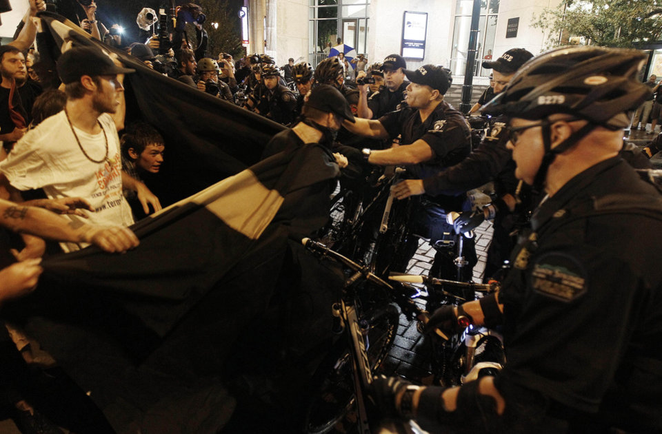 Photo - Occupy Demonstrators use a tarp to push against a police barricade during an unscheduled protest march, Tuesday, Sept. 4, 2012, in Charlotte, N.C. The Democratic National Convention begins today. (AP Photo/Gerry Broome) ORG XMIT: XDNC156
