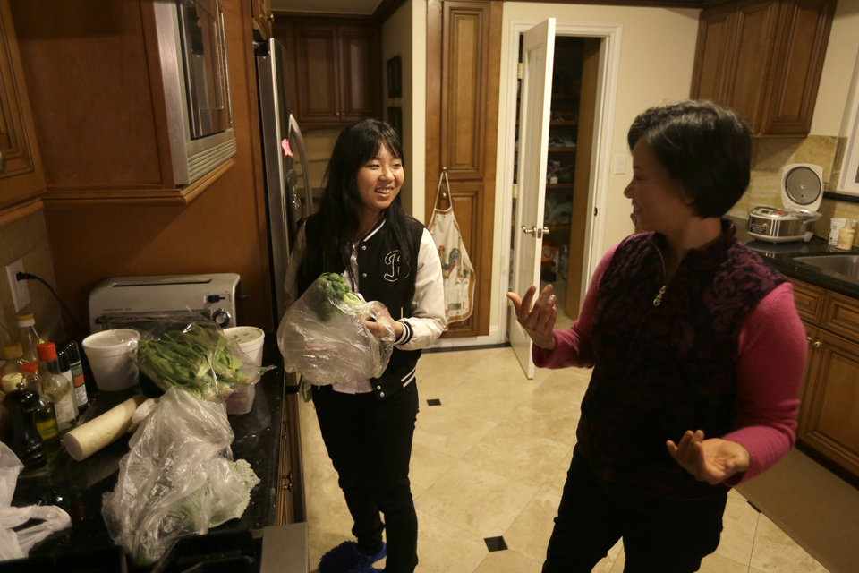 In this Monday, March 11, 2012 photo, Victoria Hu, left, helps her mother, Hong Li, in the kitchen of their house in Rancho Palos Verdes, Calif. (AP Photo/Chris Carlson)