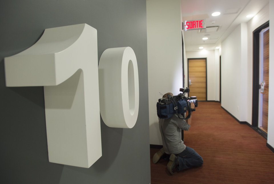 Photo - A member of the media films an apartment where three prison escapees were captured in Montreal, Sunday, June 22, 2014. The three men escaped from a Quebec City-area prison by helicopter on June 7. (AP Photo/The Canadian Press, Graham Hughes)