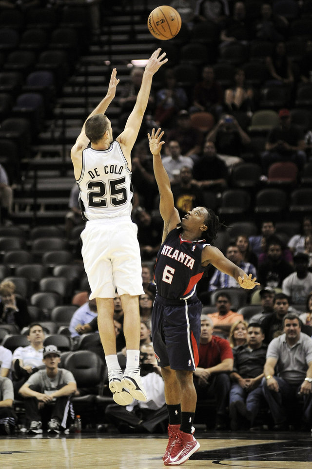San Antonio Spurs' Nando De Colo, left, of France, shoots the game-winning shot over Atlanta Hawks' Carldell Johnson during the second half of an NBA preseason basketball game, Wednesday, Oct. 10, 2012, in San Antonio. San Antonio won 101-99. (AP Photo/Darren Abate)