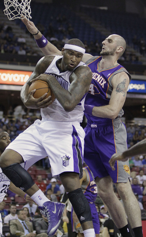 Sacramento Kings center DeMarcus Cousins, left, pulls down a rebound against Phoenix Suns center Marcin Gortat, of Poland, during the first quarter of an NBA preseason basketball game in Sacramento, Calif., Wednesday, Oct. 10, 2012. (AP Photo/Rich Pedroncelli)