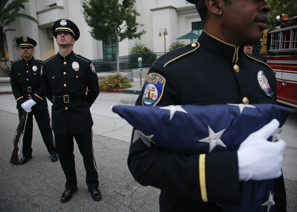 Beverly Hills Police officers gather just after dawn to remember the moment the first plane struck the World Trade Center on the 10th anniversary of 9/11 in Beverly Hills, Calif., Sunday, Sept. 11, 2011. (AP Photo/Jason Redmond)
