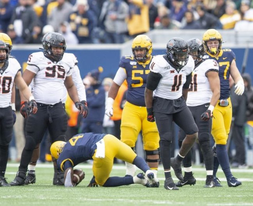 Photo -  Oklahoma State's Amen Ogbongbemiga (11) celebrates after tackling West Virginia's Leddie Brown (4) — one of his 11 tackles in a 20-13 win Saturday. [Bruce Waterfield/OSU Athletics]