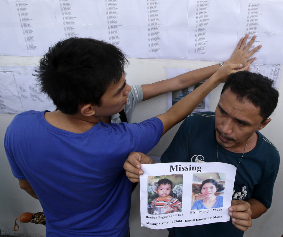 Photo - Roderick Mama holds print out of his missing wife and sons as a couple checks the list of survivors posted on the wall of the 2GO shipping company Sunday Aug. 18, 2013 in Cebu city, central Philippines. Roderick's 8-month old son Dincell survived Friday night's collision between the passenger ferry MV Thomas Aquinas and the cargo ship Sulpicio Express Siete in central Philippines.  Divers plucked two more bodies from a sunken passenger ferry on Sunday and scrambled to plug an oil leak in the wreckage after a collision with a cargo ship. The accident near the central Philippine port of Cebu that has left 34 dead and more than 80 others missing. (AP Photo/Bullit Marquez)