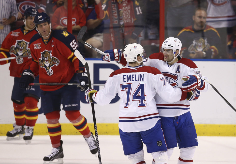 Photo - Montreal Canadiens' Alexei Emelin (74) and Max Pacioretty (67) celebrate after a goal as Florida Panthers' Ed Jocanovski (55) watches during the first period of an NHL hockey game in Sunrise, Fla., Saturday, March 29, 2014. (AP Photo/J Pat Carter)