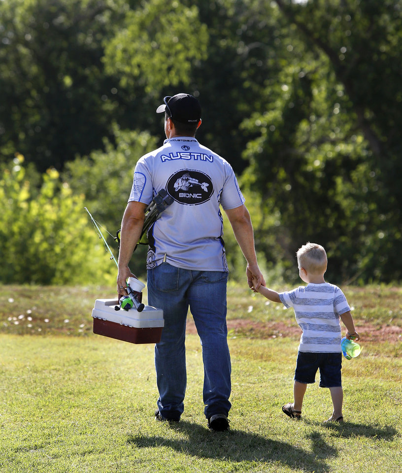 Photo - Stephen Austin carries the poles and tackle box with one hand while holding the hand of his son, Cooper, 2, with his other hand as they walk to find the