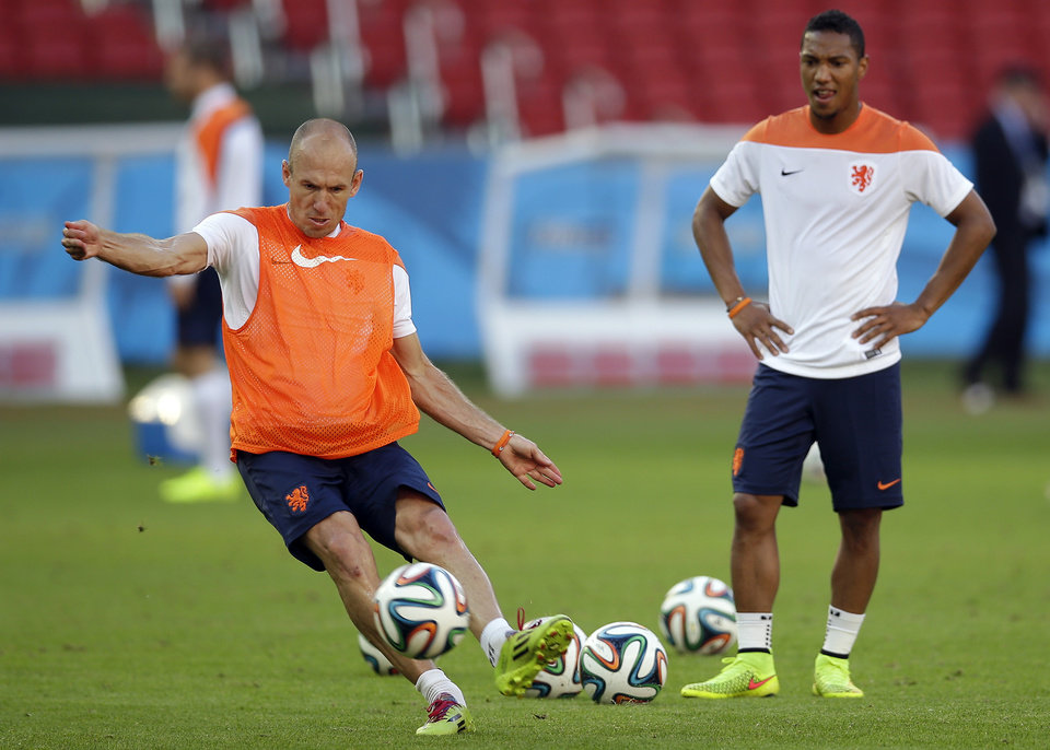 Photo - Netherlands' Arjen Robben, left, plays the ball during the official training the day before the group B World Cup soccer match between Australia and the Netherlands at the Estadio Beira-Rio in Porto Alegre, Brazil, Tuesday, June 17, 2014. At right is Netherlands' Jonathan de Guzman. (AP Photo/Michael Sohn)