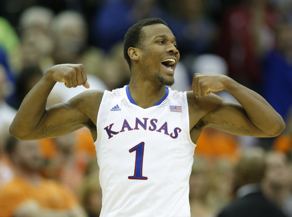 Photo - Kansas guard Wayne Selden, Jr. celebrates following an NCAA college basketball game against Oklahoma State in the quarterfinals of the Big 12 Conference men's tournament in Kansas City, Mo., Thursday, March 13, 2014. Kansas defeated Oklahoma State 77-70 in overtime. (AP Photo/Orlin Wagner)