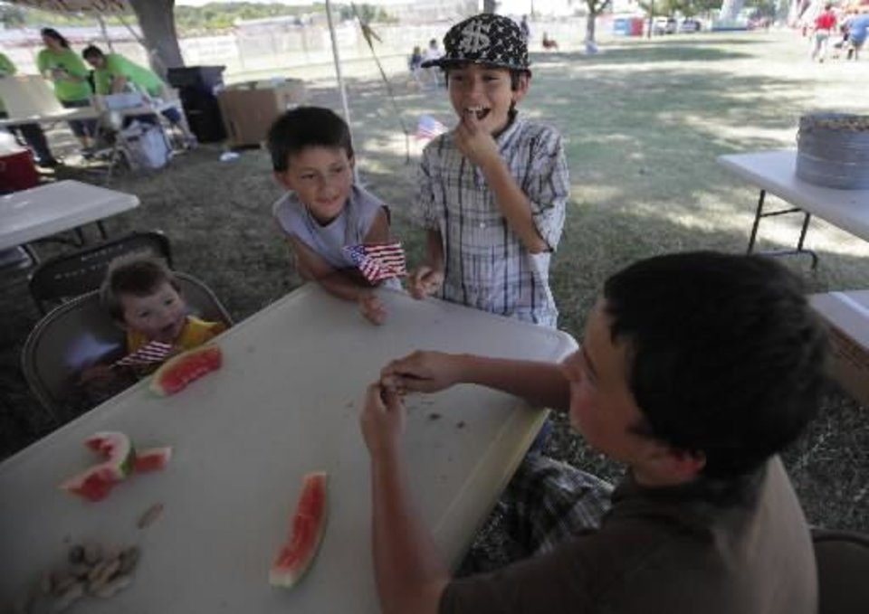 Photo - Christopher Freer, 2, Elijah Varela, 8, Raymos Estrada, 11, and Isaiah Valera, 12, eat watermelon and peanuts at a Fourth of July Celebration in Seminole, Okla., July 4, 2012. Photo by Garett Fisbeck, The Oklahoman