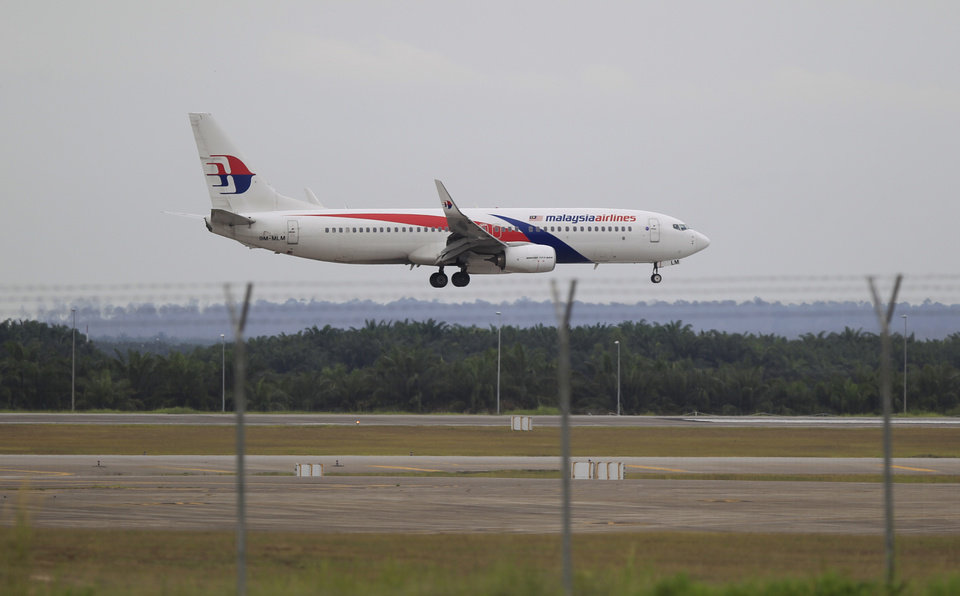 Photo - A Malaysia Airlines plane approaches to land at Kuala Lumpur International Airport in Sepang, Malaysia, Friday, Aug. 29, 2014. Malaysia Airlines will cut 6,000 workers as part of an overhaul announced Friday to revive its damaged brand after being hit by double passenger jet disasters. (AP Photo/Lai Seng Sin)