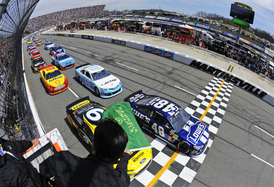 Jimmie Johnson (48) and Marcos Ambrose (9) lead the field past the green flag to start the NASCAR Sprint Cup Series STP Gas Booster 500 on April 7, 2013, at Martinsville Speedway in Martinsville, Virginia. (AP Photo/Jared C. Tilton, Pool)