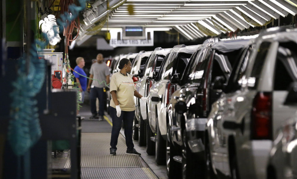Photo -  In this May 13 file photo, an auto worker inspects finished SUVs coming off the assembly line at the General Motors auto plant in Arlington, Texas. AP Photo   LM Otero -  AP