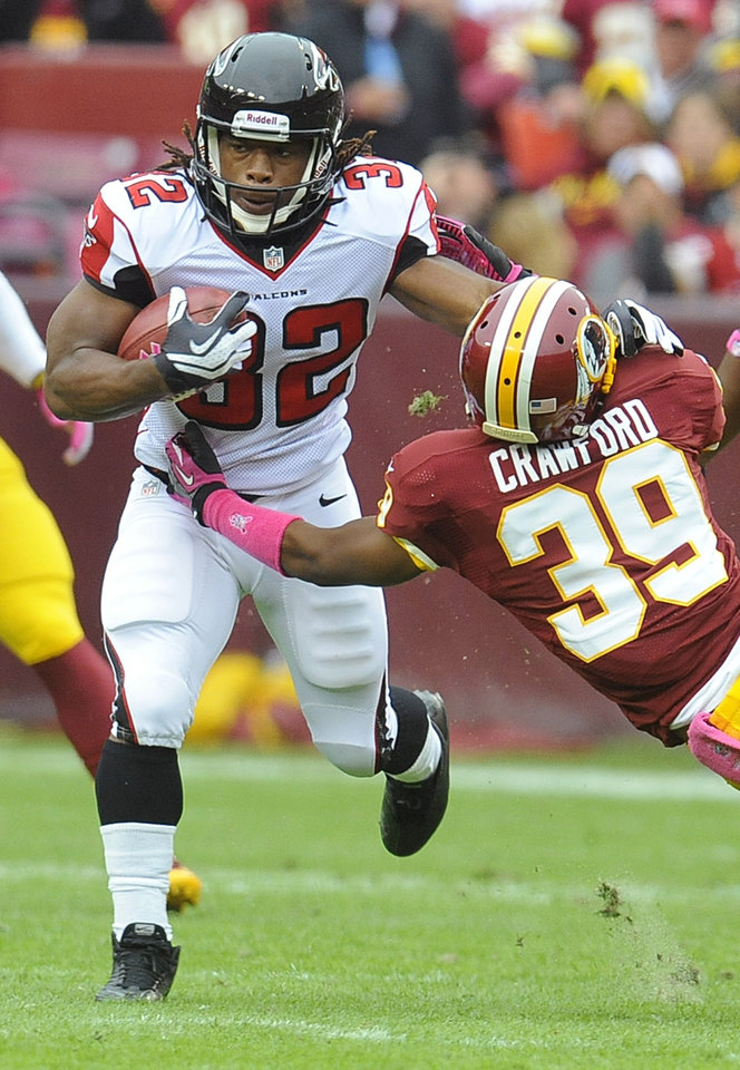 Photo -   Atlanta Falcons running back Jacquizz Rodgers pushes Washington Redskins cornerback Richard Crawford away during the first half of an NFL football game in Landover, Md., Sunday, Oct. 7, 2012. (AP Photo/Richard Lipski)