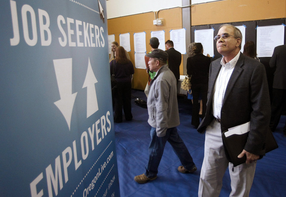 Photo -   FILE - In this April 24, 2012, file photo, job seeker Alan Shull attends a job fair in Portland, Ore. The Labor Department said Friday, May 4, 2012, that the economy added just 115,000 jobs in April. U.S. employers pulled back on hiring for the second straight month, evidence of an economy still growing only sluggishly. The unemployment rate fell to 8.1 percent, but only because more people gave up looking for work. (AP Photo/Rick Bowmer, File)
