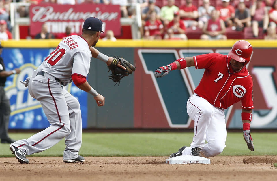 Photo - Cincinnati Reds' Ramon Santiago (7) comes up at second base for a double in front of Washington Nationals shortstop Ian Desmond (20) in the fourth inning of a baseball game on Saturday, July 26, 2014, in Cincinnati. (AP Photo/David Kohl)