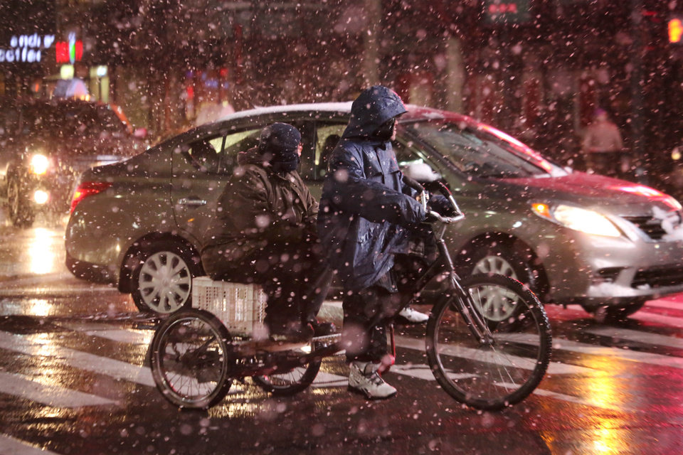 Photo - A man and his passenger ride a three-wheeled bike in the borough of Manhattan during a snow storm on Friday, Feb. 8 2013, in New York. The storm that forecasters warned could be a blizzard for the history books began clobbering the New York-to-Boston corridor on Friday, grounding flights, closing workplaces and sending people rushing to get home ahead of a possible 1 to 3 feet of snow. (AP Photo/Peter Morgan)