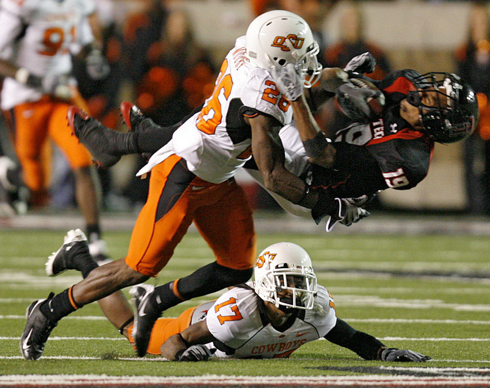 Photo - Oklahoma State's Quinton Moore (26) hits Texas Tech's Lyle Leong (19) during the second half of the college football game between the Oklahoma State University Cowboys (OSU) and the Texas Tech Red Raiders at Jones AT&T Stadium on Saturday, Nov. 8, 2008, in Lubbock, Tex.BY CHRIS LANDSBERGER/THE OKLAHOMAN