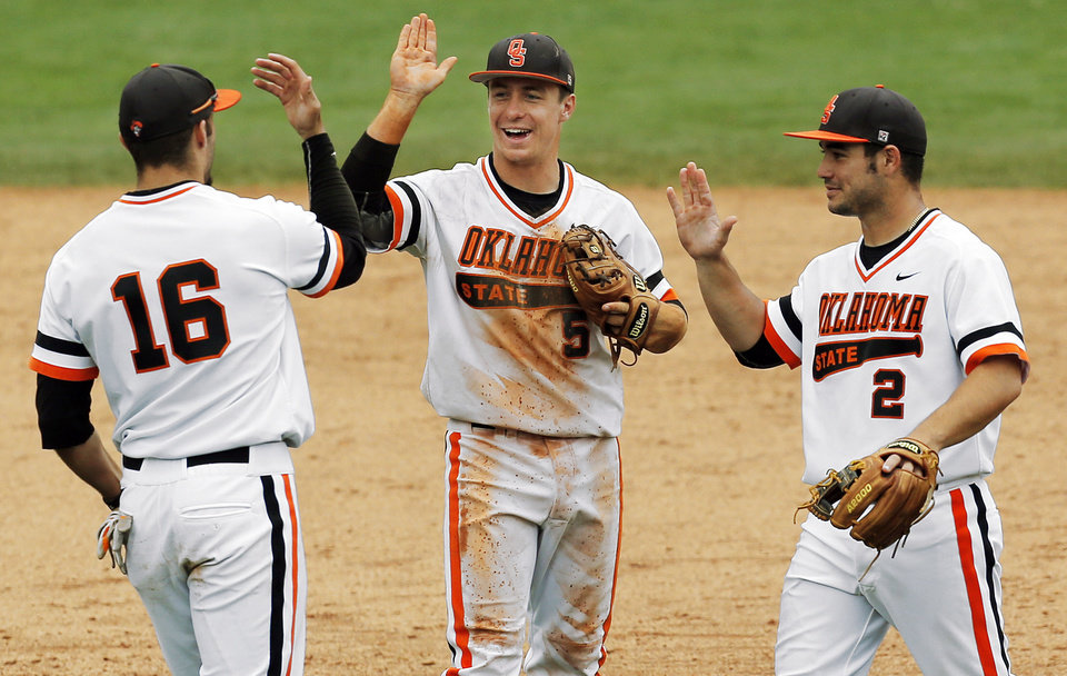 Photo - From left, OSU's Tanner Krietemeier (16), Donnie Walton (5) and Tim Arakawa (2) celebrate after a college baseball game between Texas and Oklahoma State in the Big 12 baseball tournament at the Chickasaw Bricktown Ballpark in Oklahoma City,  Saturday, May 24, 2014. OSU won 3-1 to force an elimination game. Photo by Nate Billings, The Oklahoman