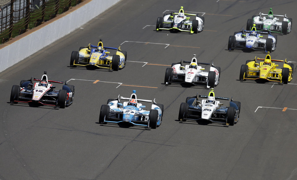Photo - The field for the the 98th running of the Indianapolis 500 IndyCar auto race heads into the first turn, lead by James Hinchcliffe, of Canada, (27), Ed Carpenter (20) and Will Power, of Australia, (12) on the start at the Indianapolis Motor Speedway in Indianapolis, Sunday, May 25, 2014. (AP Photo/Darron Cummings)