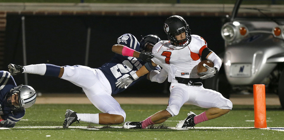 Yukon's Tyler Tredway scores a touchdown in front of Edmond North's Dante Sanders during a high school football game at Wantland Stadium in Edmond, Okla., Thursday, October 4, 2012. Photo by Bryan Terry, The Oklahoman