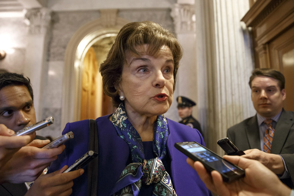Photo - Senate Intelligence Committee Chair Sen. Dianne Feinstein, D-Calif. talks to reporters as she leaves the Senate chamber on Capitol Hill in Washington, Tuesday, March 11, 2014, after saying that the CIA's improper search of a stand-alone computer network established for Congress has been referred to the Justice Department. The issue stems from the investigation into allegations of CIA abuse in a Bush-era detention and interrogation program. (AP Photo/J. Scott Applewhite)