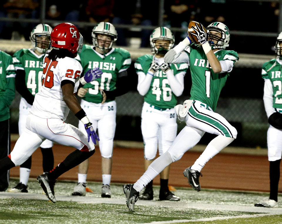 Photo - Irish receiver Cody Chancellor catches a pass and carries to the end zone on a 72 yard touchdown as the Bishop McGuinness Irish play the Carl Albert Titans in a Class 5A semi-final playoff game at Harve Collins Field on Friday, Nov. 23, 2012  in Norman, Okla. Trailing is Titan Dillon Lohr.  Photo by Steve Sisney, The Oklahoman