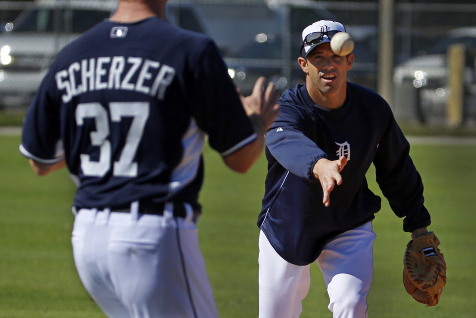 Photo - Detroit Tigers manager Brad Ausmus, right, tosses to pitcher Max Scherzer (37) during a drill on the team's first day of baseball spring training for pitchers and catchers in Lakeland, Fla., Friday, Feb. 14, 2014. (AP Photo/Gene J. Puskar)