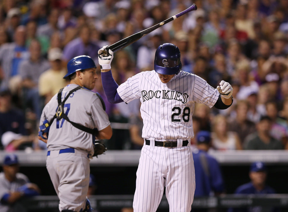 Photo - Colorado Rockies' Nolan Arenado, front, reacts after striking out with two runners on base as Los Angeles Dodgers catcher A.J. Ellis heads to the dugout at the end of the eighth inning of the Dodgers' 3-2 victory in a baseball game in Denver on Thursday, July 3, 2014. (AP Photo/David Zalubowski)