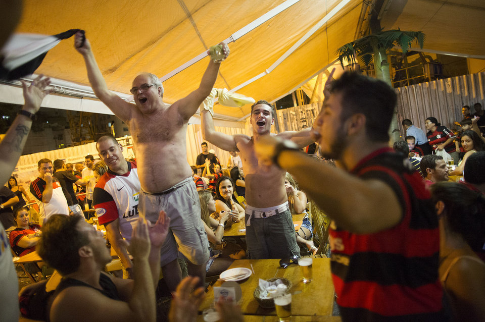 Photo - In this April 13, 2014 photo, fans of the Flamengo soccer team celebrate in a bar after their team won the Rio de Janeiro state championship against Vasco in Rio de Janeiro, Brazil. The upcoming World Cup in Brazil will be the first in the South American nation since 1950. (AP Photo/Leo Correa)