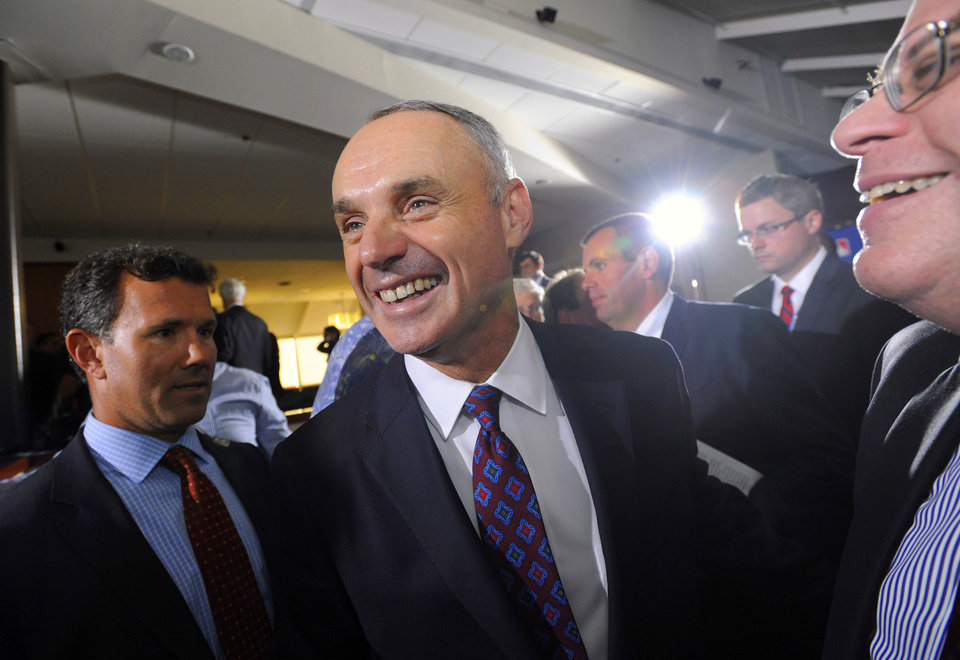 Photo - Major League Baseball Chief Operating Officer Rob Manfred, center, smiles after team owners elected him as the next commissioner of Major League Baseball during an owners quarterly meeting in Baltimore, Thursday, Aug. 14, 2014. (AP Photo/Steve Ruark)