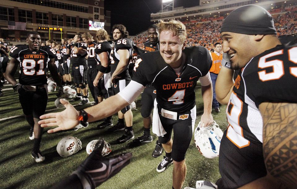 Photo - CELEBRATION: OSU's Brandon Weeden (4) celebrates with his teammates including Tolu Moala (59), right, after the college football game between Oklahoma State University (OSU) and the University of Colorado (CU) at Boone Pickens Stadium in Stillwater, Okla., Thursday, Nov. 19, 2009. OSU won, 31-28. Photo by Nate Billings, The Oklahoman ORG XMIT: KOD