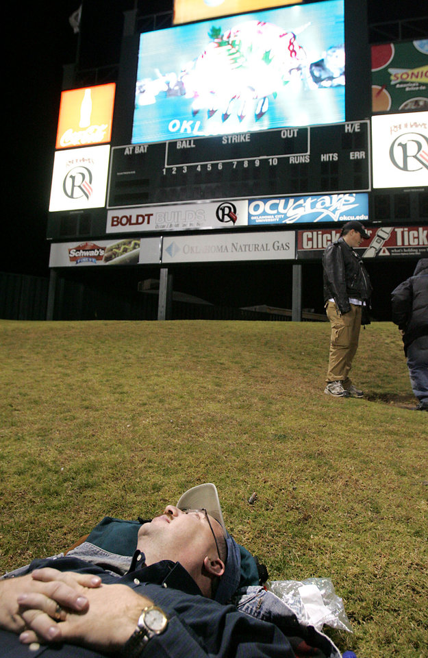 Photo - Nate Skinner, of OKlahoma City, lies on his back and watches the Centennial Spectacular upside down at the AT&T Bricktown Ballpark in Oklahoma City as part of the State's Centennial celebration. By John Clanton, The Oklahoman