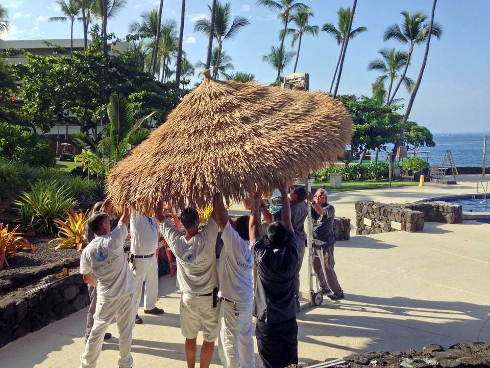 Photo - Staff members of the Royal Kona Resort in Kailua, Hawaii take down umbrellas as the resort prepares for Hurricane Iselle on Thursday, Aug. 7, 2014. Hurricane Iselle is expected to arrive on the Big Island on Thursday evening, bringing heavy rains, winds gusting up to 85 mph and flooding in some areas. Weather officials changed their outlook on the system Wednesday after seeing it get a little stronger, giving it enough oomph to stay a hurricane as it reaches landfall. (AP Photo/Chris Stewart)