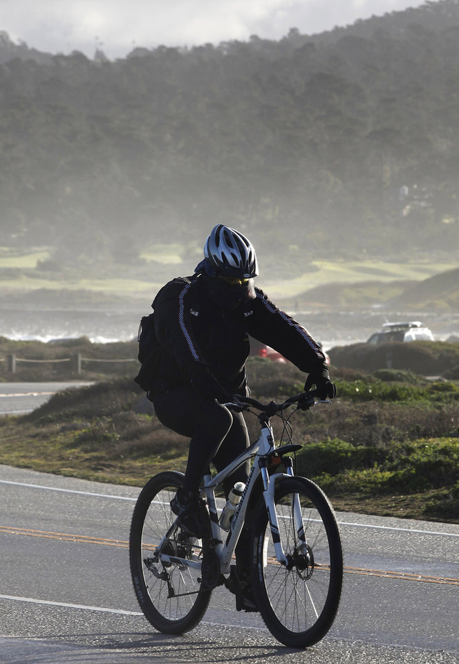 Photo - Bob Palma of Seaside, Calif. is bundled from head to toe against the cold as he rides his bike past Point Joe in Pebble Beach, Calif. on Thursday January 10, 2013.