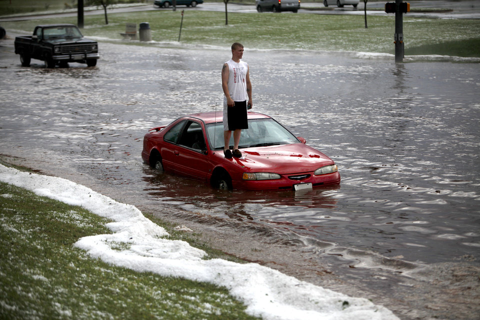 Dustin McCoy stands on the hood of his car that stalled in flood waters on Penn Avenue near Memorial Road, Sunday, May 16, 2010 in Oklahoma City. Photo by Sarah Phipps, The Oklahoman