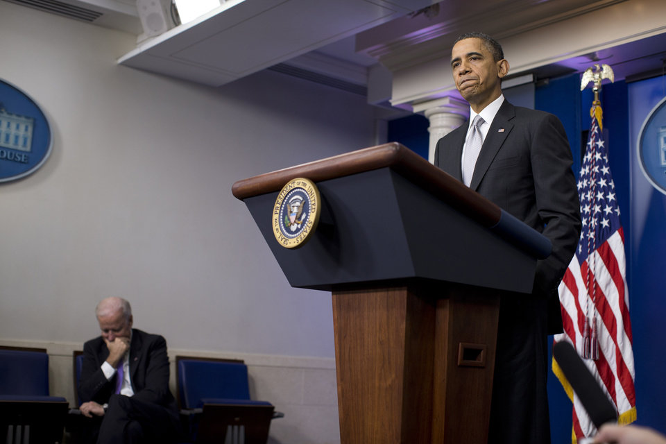 Photo - Vice President Joe Biden, left, listens as President Barack Obama pauses during remarks on the the fiscal cliff negotiations during a news conference in the briefing room of the White House on Wednesday, Dec. 19, 2012 in Washington.  Obama also announced that Biden will lead an administration-wide effort to curb gun violence in response to the Connecticut school shooting. (AP Photo/ Evan Vucci)