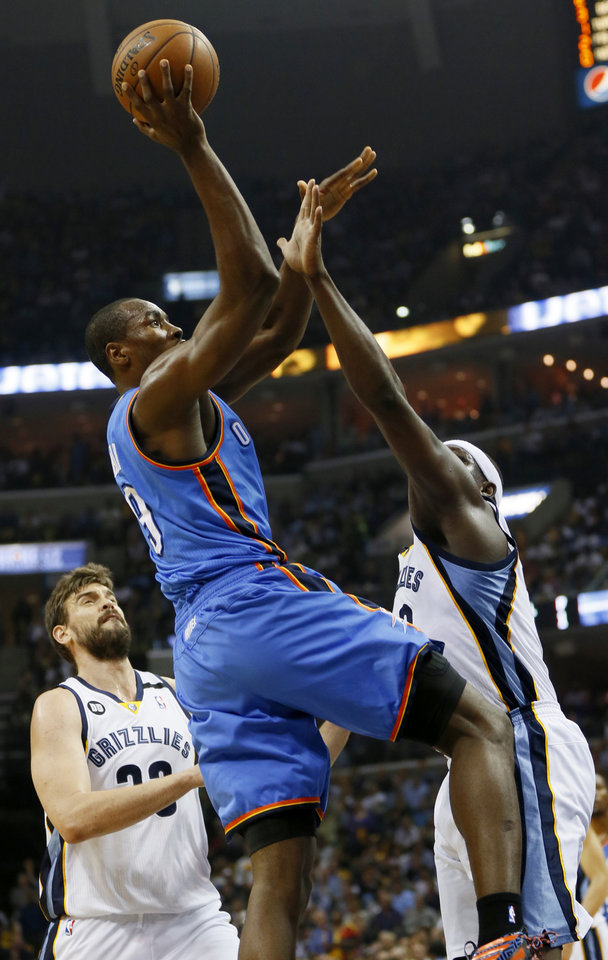 Photo - Oklahoma City's Serge Ibaka (9) shoots between Memphis' Zach Randolph (50) and Marc Gasol (33) during Game 4 of the second-round NBA basketball playoff series between the Oklahoma City Thunder and the Memphis Grizzlies at FedExForum in Memphis, Tenn., Monday, May 13, 2013. Photo by Nate Billings, The Oklahoman