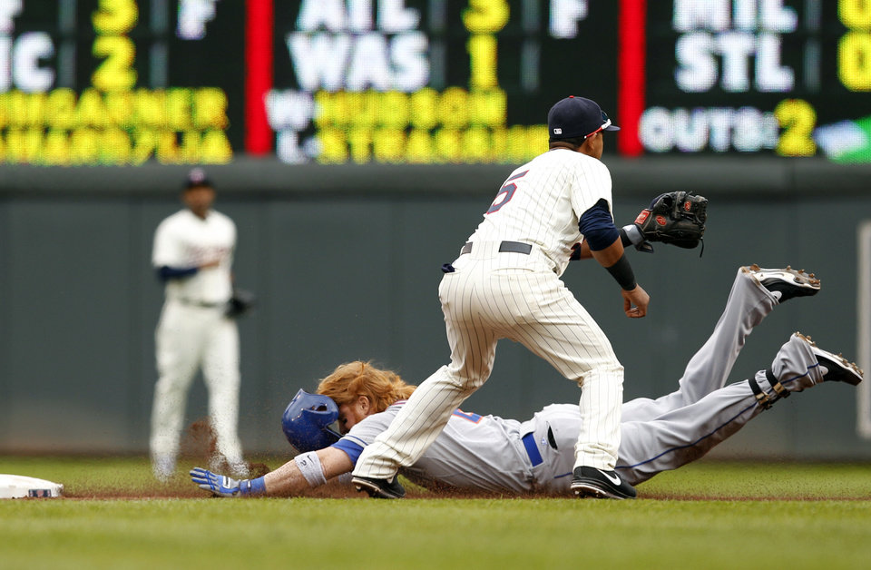 Photo - New York Mets designated hitter Justin Turner slides safely into second with a double as Minnesota Twins shortstop Eduardo Escobar (5) waits for the throw during the third inning of a baseball game Saturday, April 13, 2013, in Minneapolis. (AP Photo/Genevieve Ross)