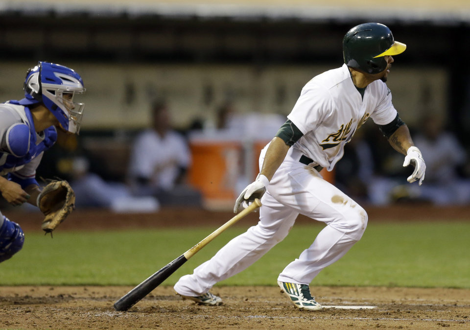 Photo - Oakland Athletics' Coco Crisp drops his bat after hitting a two run single off Texas Rangers' Yu Darvish in the second inning of a baseball game Monday, April 21, 2014, in Oakland, Calif. At left is Rangers catcher Robinson Chirinos. (AP Photo/Ben Margot)