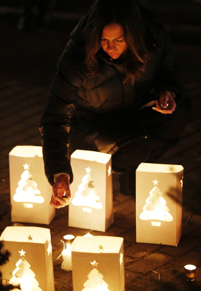 Photo - Tracy Tarantino places a candle on a makeshift memorial near the elementary school where a day earlier a gunman opened fire, Saturday, Dec. 15, 2012, in Newtown, Conn. The man, who died from a self-inflicted wound, allegedly killed his mother at their home and then opened fire Friday inside the Sandy Hook Elementary school, massacring 26 people, including 20 children. (AP Photo/Julio Cortez) ORG XMIT: CTJC141