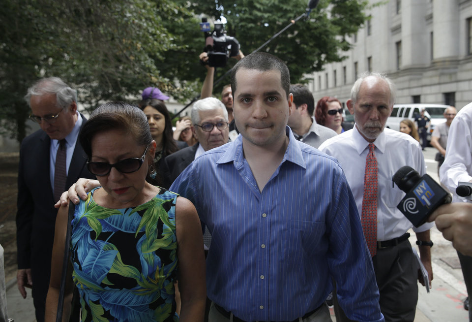 Photo - GIlberto Valle, front right, is surrounded by reporters as he leaves Manhattan federal court in New York, Tuesday, July 1, 2014. A federal judge has overturned the conviction of Valle, a former New York City police officer accused of plotting to kidnap, kill and eat young women. (AP Photo/Seth Weng)