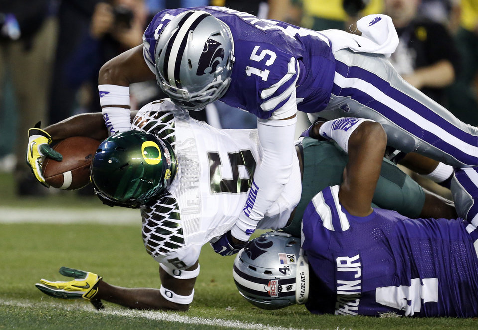 Photo - Oregon running back De'Anthony Thomas (6) scores a touchdown as Kansas State defensive back Randall Evans (15 ) and Arthur Brown (4) defend during the first half of the Fiesta Bowl NCAA college football game, Thursday, Jan. 3, 2013, in Glendale, Ariz. (AP Photo/Ross D. Franklin)