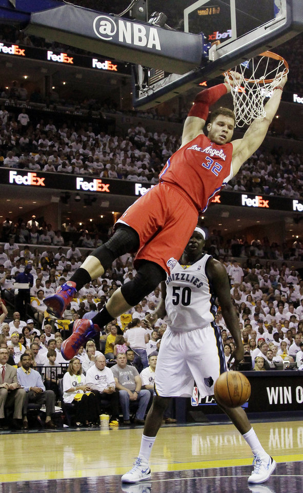 Los Angeles Clippers\' Blake Griffin (32) hangs on the basket after dunking over Memphis Grizzlies\' Zach Randolph (50) during the first half in Game 1 of a first-round NBA basketball playoff series, Sunday, April 29, 2012, in Memphis, Tenn. (AP Photo/Danny Johnston)