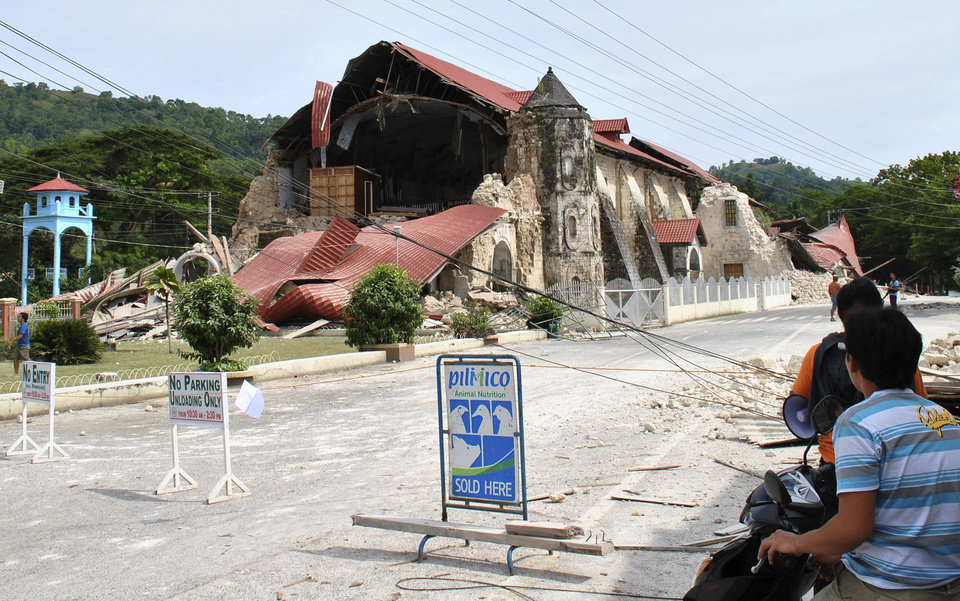Photo - Residents look at the remains of the Loboc Chruch following a 7.2-magnitude earthquake that hit Loboc, Bohol, central Philippines, Tuesday, Oct. 15, 2013. The tremor collapsed buildings, cracked roads and toppled the bell tower of the Philippines' oldest church Tuesday morning, causing multiple deaths across the central region and sending terrified residents into deadly stampedes. (AP Photo)
