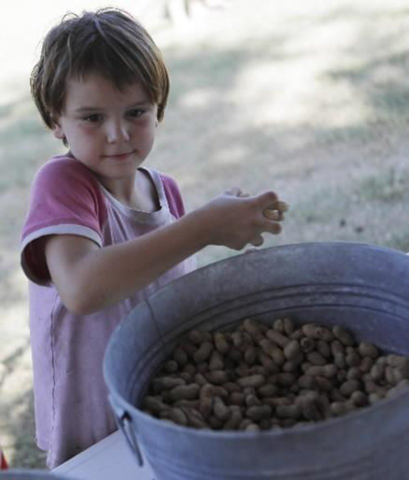 Photo - Jalynn Moore, 8, of Maud, gets a handful of peanuts at a Fourth of July Celebration in Seminole, Okla., July 4, 2012. Photo by Garett Fisbeck, The Oklahoman